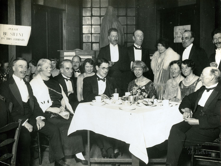Glasgow School of Art Staff at dinner in the library, featuring A. L, Mrs W. S. Shanks, Allan D. Mainds, Campbell Mackie, Mrs De Courcy Lethwaite Dewar, and P Wylie Davidson (Archive refernce: GSAA/P/1/35)