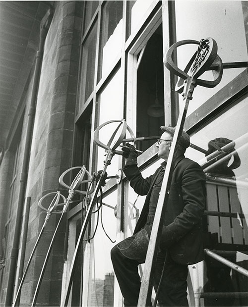 Photo of a workman repairing a window bracket on the front facade of the Mackintosh Building (Archive reference: GSAA/P/7/99)