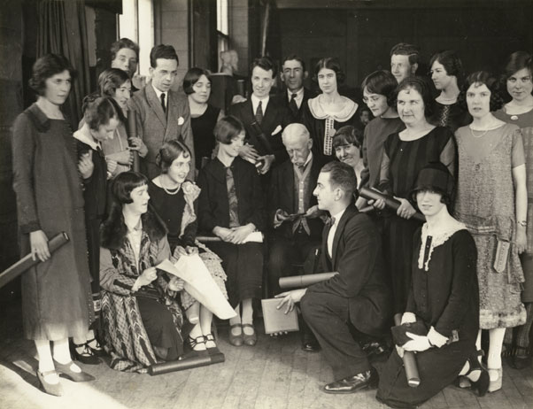 Glasgow School of Art students gathered around Patrick Smith Dunn, Governor of School, featuring Charles Cameron Baillie, Duncan Shanks (Sen), Isabel Goudie, Margaret Nairn, Nonie McCrone, Alexander McPherson, Mary Armour, Isa Cleland, Robert Milne, Betsy. 1923-1924. GSA Archives Collections. https://gsaarchives.net/archon/index.php?p=digitallibrary/digitalcontent&id=2013